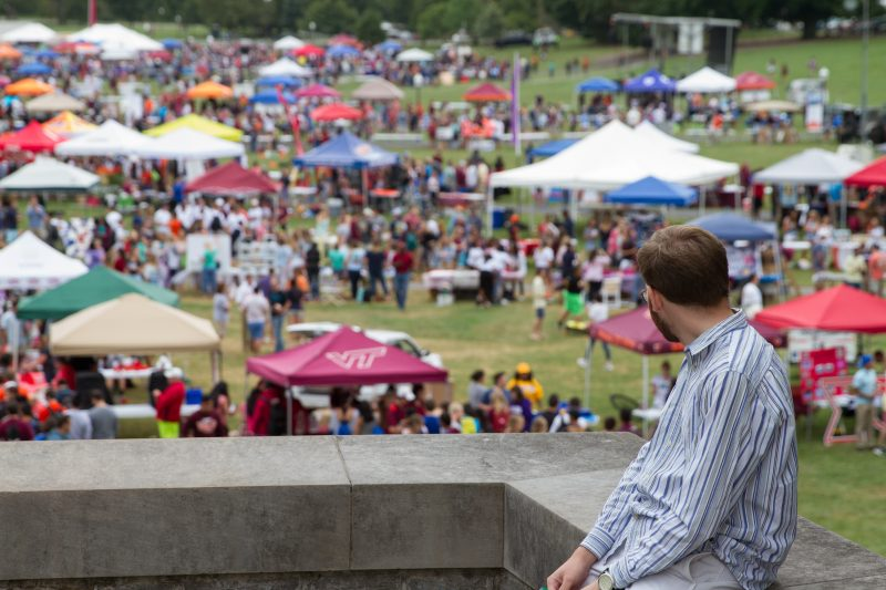 Student looks out on Gobblerfest from the Pylons